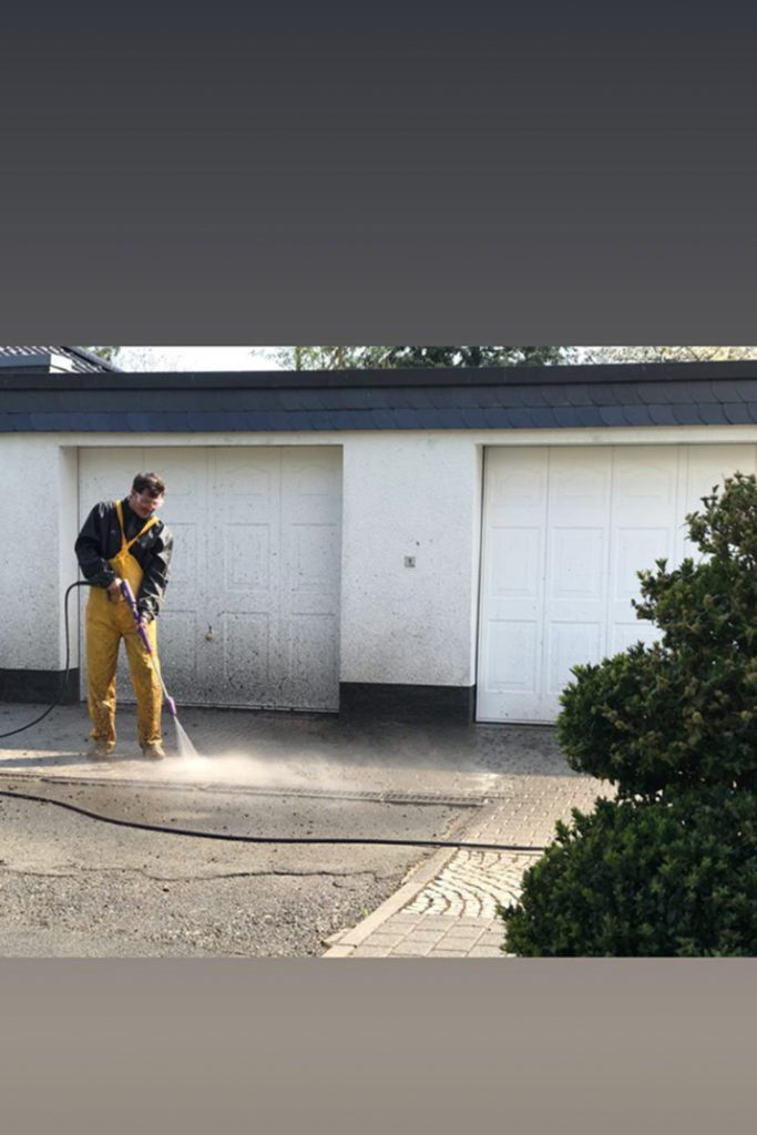 Die Garageneinfahrt mit dem Hochdruckstrahler reinigen